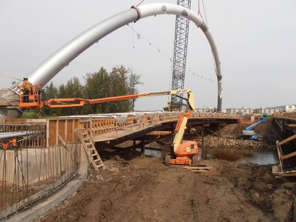 Construction of a pedestrian bridge in Alberta with pipe bent by Advanced Bending Technologies.